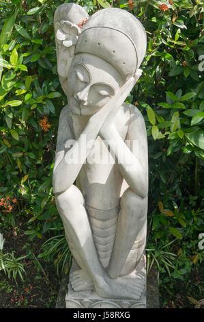 Balinesische schlafen Frauen-Statue in einem Garten umgeben von Pflanzen - Stockfoto