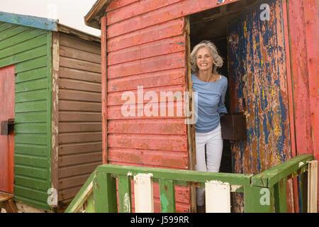 Porträt von lächelnden senior Frau am Strandhütte auf sonnigen Tag - Stockfoto