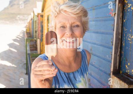 Porträt von Beautiful senior Woman Holding Eis stehend von Hütte am Strand - Stockfoto