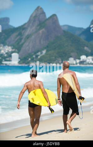Junge brasilianische Surfer zu Fuß mit ihren Surfbrettern von Arpoador, den beliebten Surfspot in Richtung Strand - Stockfoto
