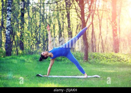 Junge Frau, die Yoga-Übungen im Sommer Stadtpark. Gesundheit-Lifestyle-Konzept. - Stockfoto