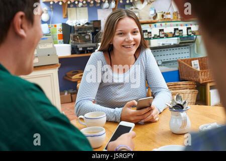 Gruppe von Jugendlichen Freunde treffen im Cafe und Benutzung von Mobiltelefonen - Stockfoto