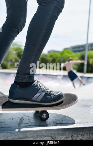Nahaufnahme eines kaukasischen Jünglings skateboarding in ein Outdoor-Skate-park - Stockfoto