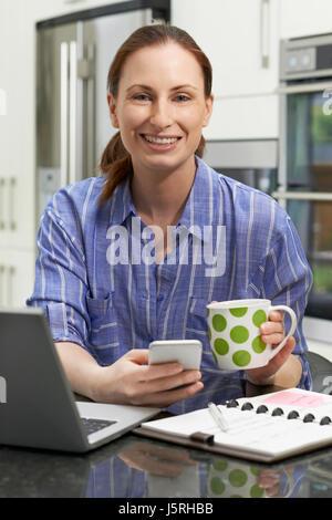 Porträt von freier Arbeitnehmerin mit Laptop In der Küche zu Hause - Stockfoto