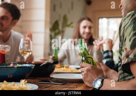 Gruppe der glückliche junge Männer sprechen und trinken Bier am Tisch zu Hause - Stockfoto