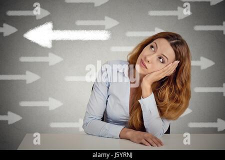 Nachdenkliche Frau, die eine Chance gegen die Strömung. Nachdenklich Geschäftsfrau sitzen am Tisch auf graue Wand - Stockfoto