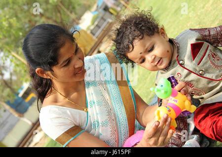 Eine Mutter macht ein ihr junge mit seinem Spielzeug spielen - Stockfoto