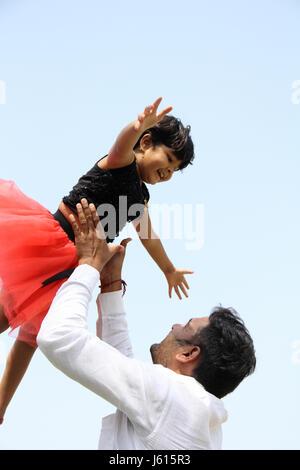 Junge indische Vater spielt mit seinem Mädchen durch das werfen, warf ihr hoch in die Luft - Stockfoto