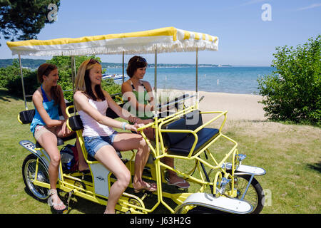 Michigan Traverse City West Arm Grand Traverse Bay Clinch Park drei Mädchen Teen Surrey vier Rad Fahrrad gelb Quadracycle - Stockfoto