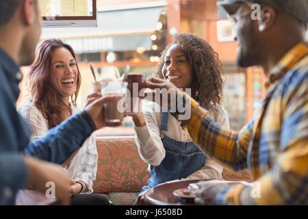 Lächelnden Freunde Toasten Kaffeetassen im café - Stockfoto