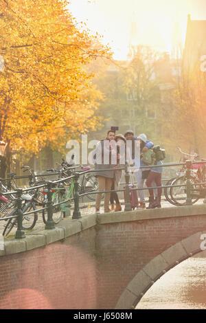 Freunde nehmen Selfie mit Selfie aufkleben Herbst Brücke über den Kanal in Amsterdam - Stockfoto