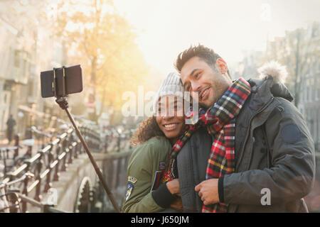 Liebevolle paar umarmt und nehmen Selfie mit Selfie stick auf Herbst Brücke, Amsterdam - Stockfoto