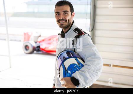 Portrait zuversichtlich männlichen Formel-1 Rennen auto fahrer mit Helm in Werkstatt - Stockfoto