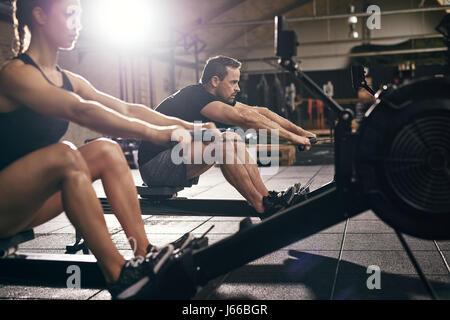 Seitenansicht von Mann und Frau, die Übungen mit Rudergerät im Fitnessstudio. - Stockfoto