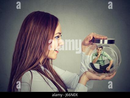 Frau hält ein Glas mit inhaftierten Mann drin - Stockfoto