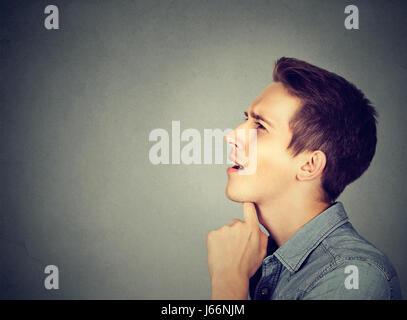 Nachdenklicher junger Mann stehend an der Wand - Stockfoto