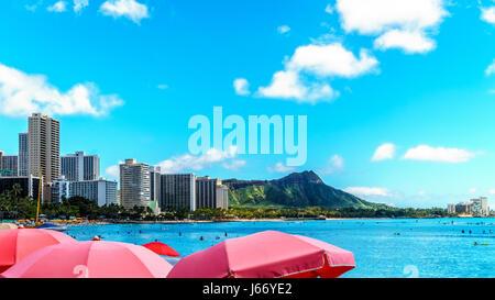 Schirme in Hülle und Fülle am Waikiki Beach mit seinen vielen Resorts unter blauem Himmel. Waikiki ist einer der - Stockfoto