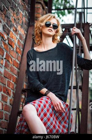 Schöne junge Grunge (Rock) Mädchen tragen Faltenrock, Bluse und Brille sitzt auf der Treppe - Stockfoto
