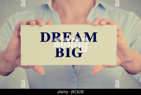 Retro-Instagram Stil Bild Geschäftsfrau Händen hielt weiße Karte mit Traum großen Satz Text Zeichen auf graue Wand - Stockfoto