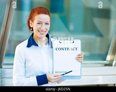 Closeup Portrait lächelnde junge Geschäftsfrau, Mitarbeiter des Unternehmens hält Vertragsdokument zeigen mit Stift - Stockfoto