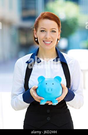 Closeup Portrait glücklich, Lächeln, Geschäftsfrau, Bankangestellter mit Sparschwein, isoliert im freien Unternehmenszentrale - Stockfoto