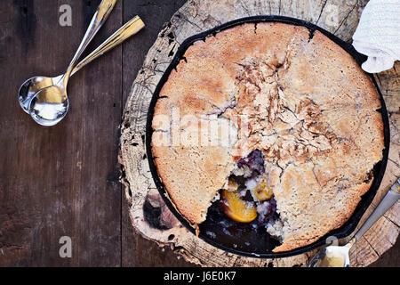 Über dem Bild eines Heidelbeere und Pfirsich Schuster über eine rustikale Holz Tischplatte in einer gusseisernen - Stockfoto