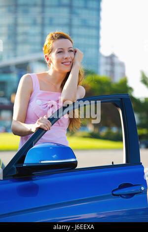 Porträt, glücklich lächelnde junge attraktive Frau Käufer stehen neben ihr neues blaues Auto außen Händler Autohaus - Stockfoto