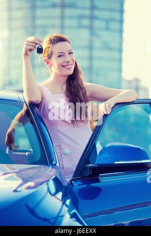 Porträt glücklich lächelnde junge attraktive Frau Käufer stehen neben neuen blaues Auto zeigen, Schlüssel isoliert - Stockfoto