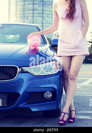 Zugeschnittenes Bild Frau Kunde, Agent neben Neuwagen, Sparschwein auf Motorhaube isoliert außerhalb im Freien steht. - Stockfoto