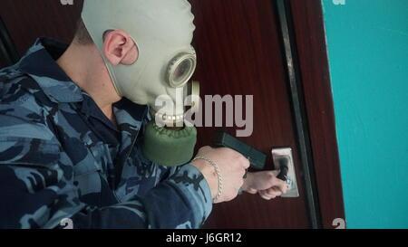 Wache in Militäruniform in eine Gasmaske gekleidet - Stockfoto