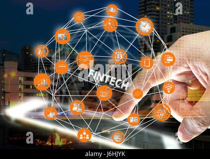 FinTech Anlagekonzept finanzielle Internet Technologie. Symbol, Nacht verschwimmen Gebäude, Smartphone, Finger und - Stockfoto