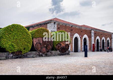 Hafen von Venedig, Castello, Arsenale. Industrielle rostigen alten Eisen Fass Behälter abgedeckt Efeu neben historischen - Stockfoto