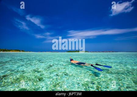 Junger Mann Schnorcheln in tropischen Lagune mit über Wasser-Bungalows, Malediven - Stockfoto