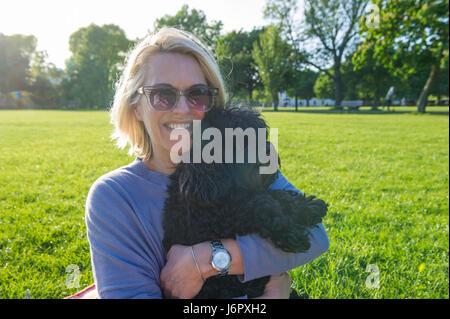 Eine Frau mittleren Alters auf ein Picknick mit ihrem kleinen schwarzen Hund - Stockfoto