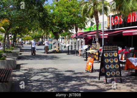 Touristen gehen und Essen an einem Baum gesäumten Allee mit Geschäften und Cafés in Playa de Las Americas auf der - Stockfoto