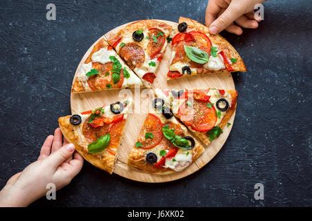 Menschen Hände nehmen Scheiben der italienischen Pizza. Italienische Pizza und Hände hautnah auf schwarzem Hintergrund. - Stockfoto
