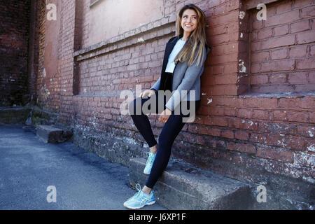 Junges Mädchen in einem Sportwear streckt vor der städtischen roten Backsteinmauer. Phot wurde an einem sonnigen - Stockfoto