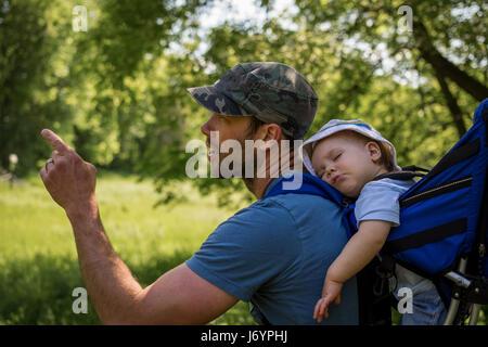 Vater mit schlafenden Baby im Rucksack wandern - Stockfoto