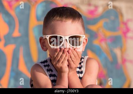 Cooler kleine Junge Sonnenbrille geschlossen seinen Mund mit Händen Keepeng Stille auf Graffiti Hintergrund - Stockfoto