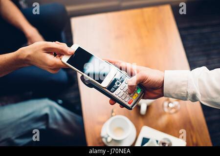 Business-Mann eine kontaktlose Smartphone Zahlung vornehmen. - Stockfoto