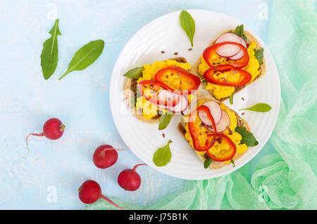 Sandwich mit Rührei, Rucola, Radieschen, Paprika Kapi und Leinsamen auf einer Platte auf einem hellen Hintergrund. - Stockfoto