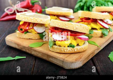 Sandwich mit Rührei, Rucola, Radieschen, Paprika Kapi und Leinsamen auf ein Schneidebrett auf einem dunklen Hintergrund - Stockfoto