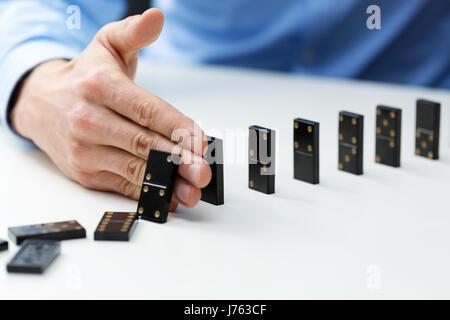 Geschäftsmann, Domino-Effekt - Business Konzept zur Problemlösung zu stoppen - Stockfoto