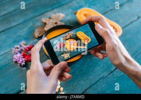Nahaufnahme der Hände des Mannes, die Aufnahme von Sahne Kürbissuppe mit smartphone - Stockfoto