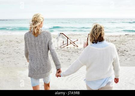 Mutter und Tochter am Strand, gehen Hand in Hand - Stockfoto