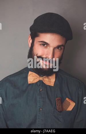 Porträt des bärtigen Mannes tragen, Kappe, Jeanshemd, Kork Fliege Holzkämme für Bart und Schnurrbart in der Hosentasche - Stockfoto