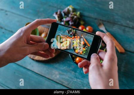 Nahaufnahme des Mannes Hände unter Bild von Avocado-Salat mit smartphone - Stockfoto
