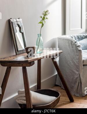 Rustikale Hocker im Schlafzimmer neben kleinen Sessel gepolstert in Leinen aus Rose uniacke - Stockfoto