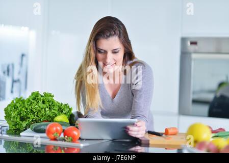 Junge Frau macht Online-shopping von Tablet-Computer. Hausfrau gefunden neues Rezept für die Zubereitung in der - Stockfoto