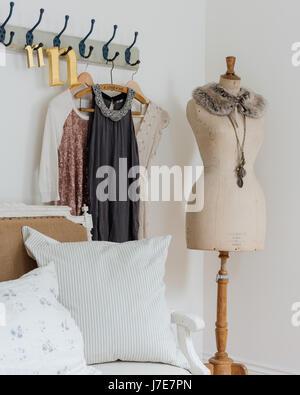Elegante Schaufensterpuppe im Schlafzimmer mit rustikaler Kleiderhaken und Kissen aus Kohl & Rosen - Stockfoto